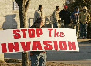 "William Daber, a Farmingville resident, holds a sign that reads ""Stop The Invasion"" as he looks back at day laborers in Farmingville, N.Y., Saturday, Jan. 7, 2006. (AP Photo/Ed Betz)"